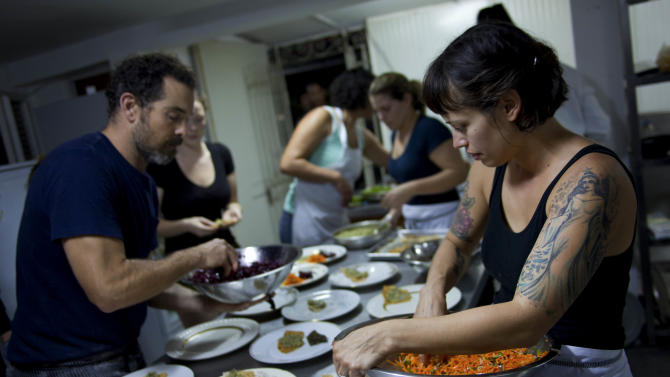 "In this Dec. 7, 2012 photo, U.S. chefs Melissa Hernandez, right, and Charlie Hallowell, left, prepare dinner for guests at the privately-run restaurant Le Chansonnier in Havana, Cuba. Hernandez and Hallowell visited Cuba as part of the ""Planting Seeds"" delegation that held give-and-take seminars with chefs and culinary students about slow food. They also put on two dinners including a rabbit-based meal at the privately run Le Chansonnier and toured nearby organic farms that grow pesticide-free produce. (AP Photo/Ramon Espinosa)"