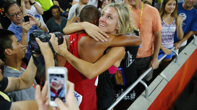 Eaton hugs hifs wife after his 1500 metres heat to win the men's decathlon at the 15th IAAF Championships in Beijing