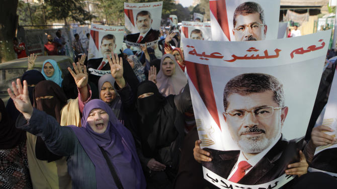 """Supporters of Egypt's ousted President Mohammed Morsi, pictured, hold up four fingers, a sign that protesters say symbolizes the Rabaah al-Adawiya mosque in Cairo that was cleared last week by Egyptian security forces, as they march in Maadi, Cairo, Egypt, Monday, Aug. 19, 2013. Arabic on posters reads, """"Yes to legitimacy, no to the coup."""" (AP Photo/Amr Nabil)"""