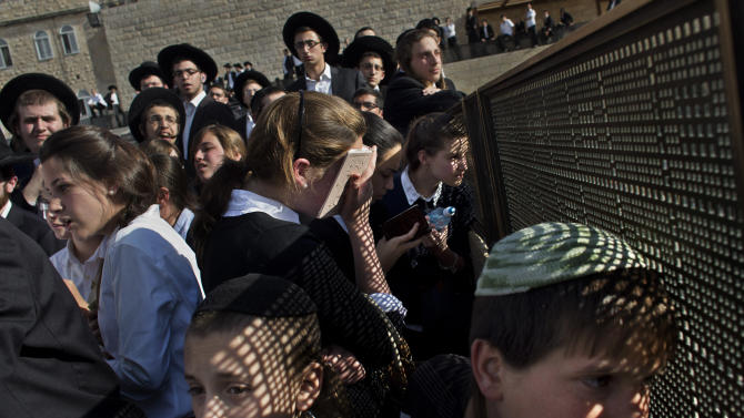 """Ultra-orthodox Jewish people gather during a protest against a prayer organized by the """"Women of the Wall"""" organization, not pictured, at the Western Wall, the holiest site where Jews can pray in Jerusalem's old city, Friday, May 10, 2013. The """"Women of the Wall"""" group has been holding monthly prayer services on the first day of the Hebrew month at the Western Wall in Jerusalem for more than two decades, wearing prayer shawls and performing religious rituals reserved for men under Orthodox Judaism. Accused by ultra-Orthodox leaders of violating """"local custom"""" at the holy site, many members have been arrested. On Friday the tables were turned because of the court ruling. Police protected the women and arrested three ultra-Orthodox men for disorderly conduct, police spokesman Micky Rosenfeld said. (AP Photo/Bernat Armangue)"""