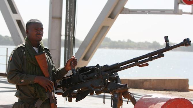A Malian soldier stands guard in front of a strategic bridge in Markala, approximately 40 km outside Segou on the road to Diabaly, in central Mali, Thursday, Jan. 17, 2013. Fighting raged in one Mali town, airstrikes hit another and army troops raced to protect a third, on Thursday, the seventh day of the French-led military intervention to wrest back Mali's north from al Qaida-linked groups. (AP Photo/Harouna Traore)