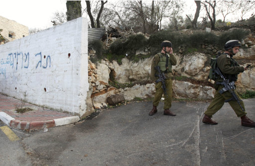 Israeli soldiers walk past a wall with a Hebrew graffiti reading