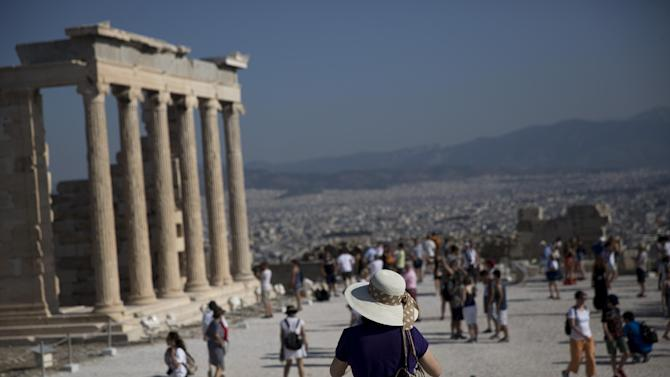 Tourist walk past the 5th century BC Erechtheion temple on the Acropolis hill, with the city of Athens in the background, on Tuesday, July 7, 2015. Greek Prime Minister Alexis Tsipras was heading Tuesday to Brussels for an emergency meeting of eurozone leaders, where he will try to use a resounding referendum victory to eke out concessions from European creditors over a bailout for the crisis-ridden country. (AP Photo/Petros Giannakouris)