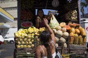 Fernanda Bolivar buys vegetables from a street vendor …