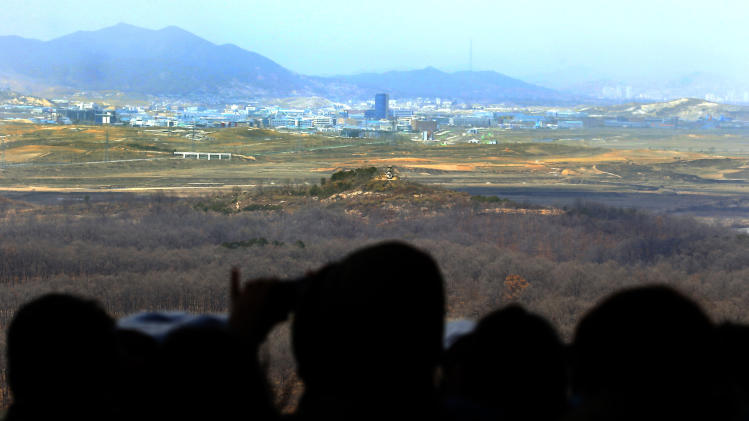 Visitors look over the North-South Korea industrial complex in Kaesong, North Korea, through binoculars at Dora Observation Post in the demilitarized zone (DMZ) near the border village of Panmunjom, in Paju, South Korea, Tuesday, April 9, 2013. The massive industrial park the rival Koreas have jointly run for nearly decade was a virtual ghost town Tuesday, its South Korean managers left to wander past shutdown assembly lines or stuff their cars to the brim with whatever goods would fit before heading south for the Demilitarized Zone that divides the nations. (AP Photo/Won Dae-hyun)  KOREA OUT