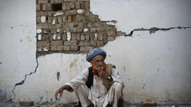 In this Tuesday, March 19, 2013 photo, an Afghan man sits among the debris of a destroyed school in the village of Budyali, Nangarhar province, Afghanistan. Taliban militants attacked the nearby district headquarters in July 2011, then took refuge in the school. The Afghan National Army requested help from coalition forces, who responded with drones, fighter jets and rockets, leaving the school destroyed, according to village elders. (AP Photo/Anja Niedringhaus)