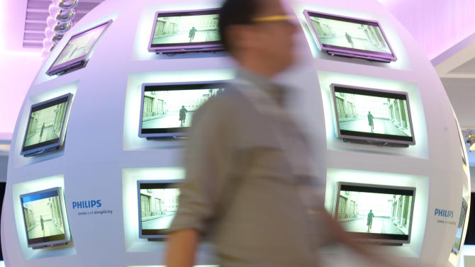 FILE - In this Wednesday, Sept. 1, 2010 file photo, a man walks in front of Philips television screens in Berlin, Germany. Royal Philips Electronics NV, the maker of electric shavers, light bulbs and medical imaging equipment, announced Monday, Oct. 22, 2012, that  earnings more than doubled in the third quarter, thanks to modest growth at all its business lines as well as the disposal of its loss-making television business. (AP Photo/Gero Breloer, File)