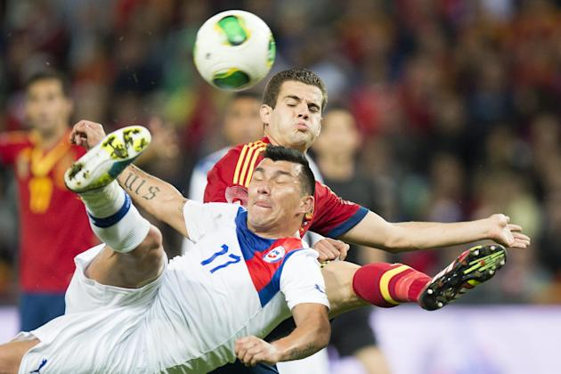 "Spain's Jose Ignacio Fernandez ""Nacho"", back, challenges for the ball with Chile's  Gary Medel, front, during a friendly soccer match between Spain and Chile at the Stade de Geneve stadium, in Geneva,"