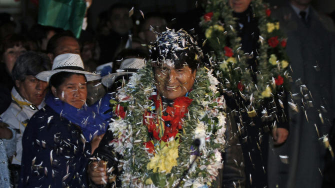 Bolivia's President Evo Morales is welcomed upon his arrival home after an unplanned 14-hour layover in Vienna at the airport in El Alto, Bolivia, Wednesday, July 3, 2013. The European rerouting of the Bolivian presidential plane over suspicions that National Security Agency leaker Edward Snowden was aboard ignited outrage Wednesday among Latin American leaders who called it a stunning violation of national sovereignty and disrespect for the region. (AP Photo/Juan Karita)