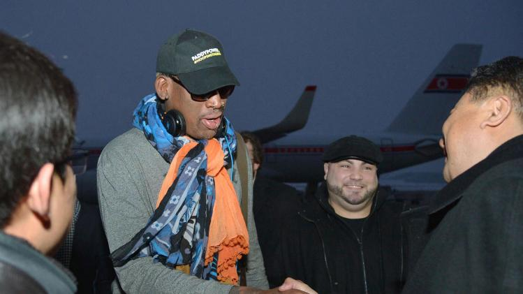 Retired U.S. basketball star Dennis Rodman shakes hands with officials upon arrival at Pyongyang airport