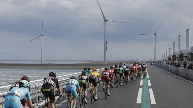 The pack passes over a barrier, part of the Deltaworks protecting the country from the sea, during the second stage of the Tour de France cycling race over 166 kilometers (103 miles) with start in Utrecht and finish in Neeltje Jans, Netherlands, Sunday, July 5, 2015. (AP Photo/Laurent Cipriani)