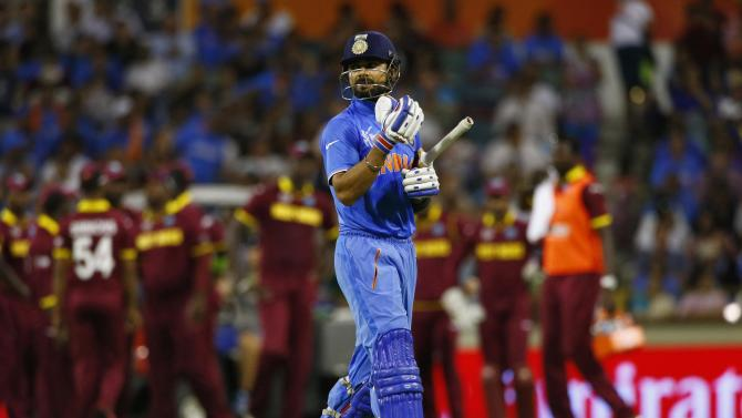 India's batsman Virat Kohli walks off the field after he was caught out by West Indies Marlon Samuels during their Cricket World Cup match in Perth
