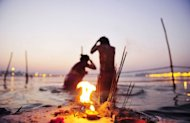 Hindu devotees bathe at Sangam, the confluence of the Yamuna, Ganges and mythical Saraswati rivers after sundown at the Kumbh Mela in Allahabad on February 9, 2013