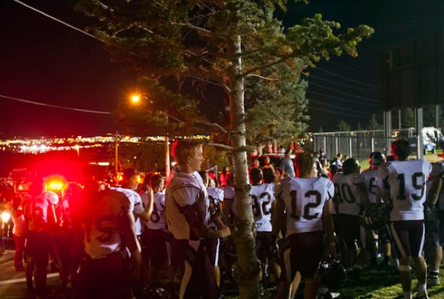 Jordan football players wait outside the East stadium after a fire suspended their game — Salt Lake Tribune