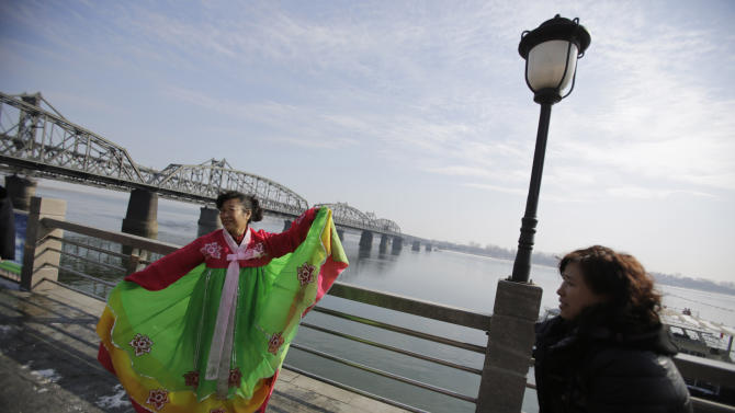 In this Feb. 6, 2013 photo, a tourist wears a traditional Korean dress to have a souvenir photo taken by a Chinese vendor with a backdrop of the Friendship Bridge linking China and North Korea in the Chinese border city of Dandong, China, opposite the North Korean border town of Sinuiju. China's patience with North Korea is wearing thin, and a widely-expected nuclear weapons test by the latter could bring that frustration to a head. Beijing signaled its growing unhappiness by agreeing to tightened U.N. sanctions after North Korea launched a rocket in December, eliciting harsh criticism from Pyongyang and comment from China watchers surprised by Beijing's unusually tough line. (AP Photo/Eugene Hoshiko)