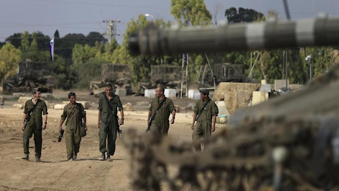 Israeli soldiers and armor gather near the Israel and Gaza Strip border, Saturday, July 5, 2014. The Israeli military says Palestinian militants have fired more than 150 rockets at southern Israel in recent weeks and Israel sent troops to the Gaza border as a precaution Thursday. The air force has responded with airstrikes on about 70 targets in Gaza, the military said. There was talk of the sides seeking a truce on Friday. (AP Photo/Tsafrir Abayov)