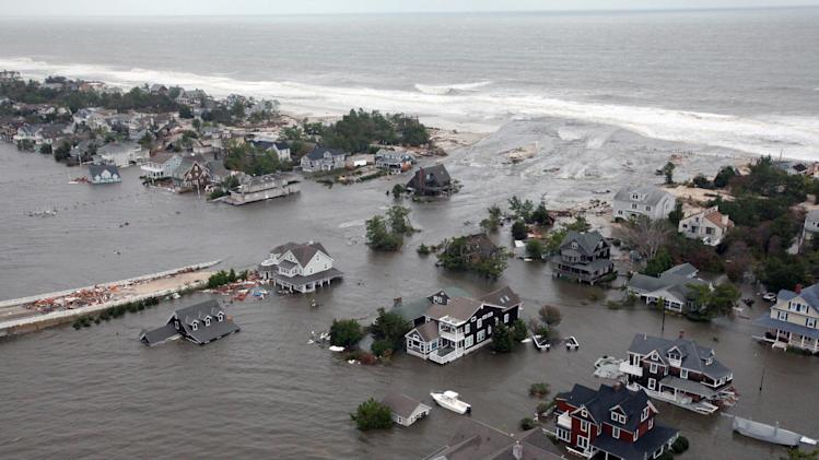 FILE - This Oct. 30, 2012 aerial file photo provided by the U.S. Air Force shows flooding on the New Jersey shoreline during a search and rescue mission by the New Jersey Army National Guard following Superstorm Sandy. Redrawn federal maps indicating flood-prone areas may force many property owners, especially in New York or New Jersey, to pay exorbitantly for flood insurance, raise their homes or move away altogether. In New Jersey, flood insurance premiums could cost as much as $31,000 a year. (AP Photo/U.S. Air Force, Master Sgt. Mark C. Olsen, File)