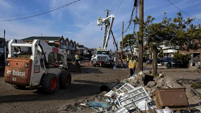 A crew with Salt River Project of Arizona (SRP) works on replacing a pole on a sand and debris-covered street in the Belle Harbor neighborhood of the borough of Queens, New York, Monday, Nov.12, 2012, in the wake of Superstorm Sandy. SRP is one of several out of the region utility companies aiding local utilities. (AP Photo/Craig Ruttle)
