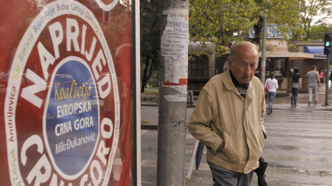 "A man passes by ruling coalition election poster reading ""Go for it, Montenegro"",  in downtown Podgorica, Montenegro, Friday, Oct. 12, 2012, two days ahead of parliamentary elections scheduled for upcoming October 14.  Montenegro's ruling coalition of longtime leader Milo Djukanovic is again a favorite to win weekend parliamentary elections in the tiny Balkan nation seeking membership in the European Union. (AP Photo/Risto Bozovic)"