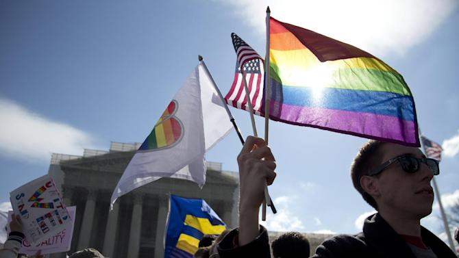Kevin Coyne of Washington holds flags in front of the Supreme Court in Washington, Wednesday, March 27, 2013. The U.S. Supreme Court, in the second day of gay marriage cases, turned Wednesday to a constitutional challenge to the federal law that prevents legally married gay Americans from collecting federal benefits generally available to straight married couples.  (AP Photo/Carolyn Kaster)