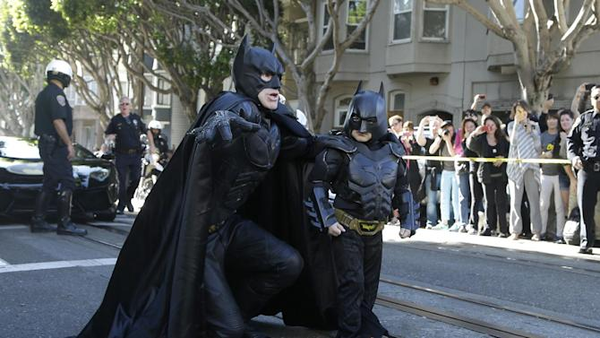 """AP10ThingsToSee - Miles Scott, dressed as Batkid, right, walks with Batman before saving a damsel in distress in San Francisco, Friday, Nov. 15, 2013. San Francisco turned into Gotham City on Friday, as city officials helped fulfill Scott's wish to be """"Batkid.""""Scott, a leukemia patient from Tulelake in far Northern California, was called into service on Friday morning by San Francisco Police Chief Greg Suhr to help fight crime, The Greater Bay Area Make-A-Wish Foundation says. (AP Photo/Jeff Chiu)"""