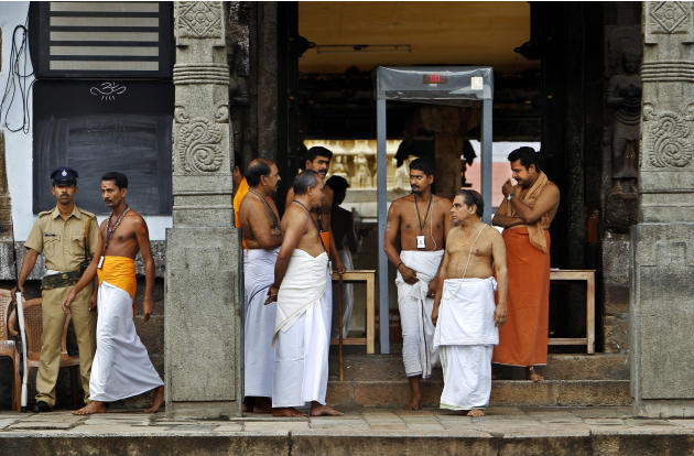 A policeman stands guard as temple staff crowd at the north side entrance of the 16th century Sree Padmanabhaswamy Temple in Trivandrum, India, Wednesday, July 6, 2011. Inside the temple are staggered