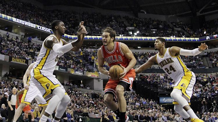 Chicago Bulls' Joakim Noah, center, goes to the basket against Indiana Pacers' Roy Hibbert, left, and Paul George during the first half of an NBA basketball game, Sunday, March 3, 2013, in Indianapolis. (AP Photo/Darron Cummings)