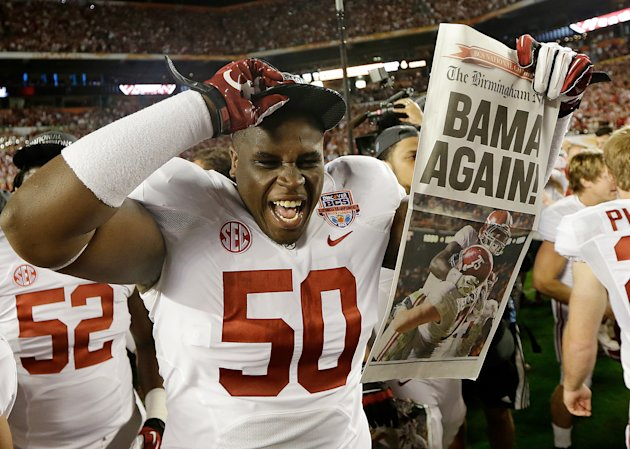 Alabama defensive lineman Alphonse Taylor (50) holds up a newspaper after the BCS National Championship college football game Monday, Jan. 7, 2013, in Miami. Alabama won 42-14. (AP Photo/David J. Phil