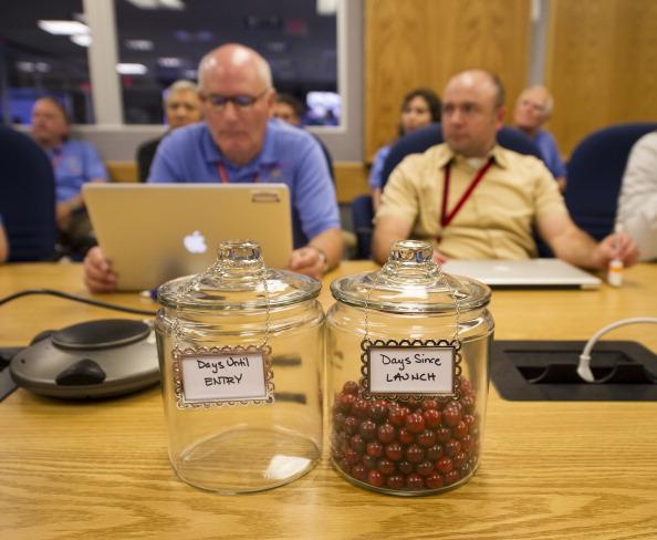 In this handout image provided by NASA, An empty jar marked 'Days Until Entry' and a jar full of marbles marked 'Days Since Launch' sit on a conference room table during a meeting of the Mars Science