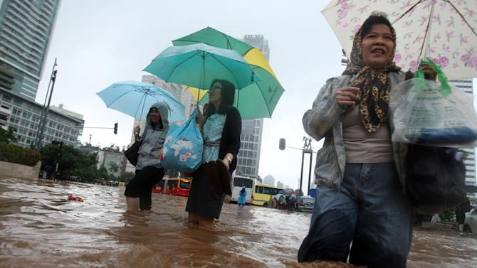 Women wade through a flooded street in Jakarta, Indonesia, Thursday, Jan. 17, 2013. Flooding caused by monsoon rains have forced thousands of people to flee their homes in Indonesia's capital. (AP Photo/Achmad Ibrahim)