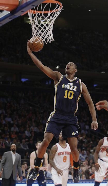 Utah Jazz's Alec Burks (10) drives past New York Knicks' J.R. Smith (8) during the first half of an NBA basketball game on Friday, March 7, 2014, in New York