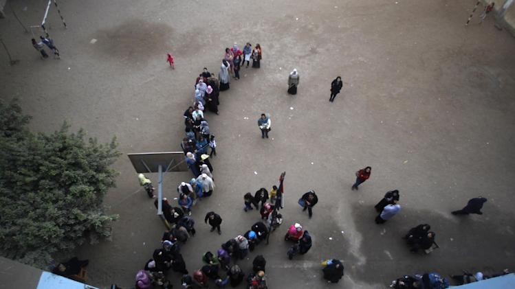 Egyptian women line up before casting their votes in a referendum on a disputed constitution drafted by Islamist supporters of President Mohammed Morsi in Cairo, Egypt, Saturday, Dec. 15, 2012. (AP Photo/Petr David Josek)