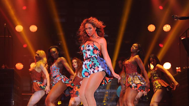 "Singer Beyonce performs the song ""Grown Woman"" on her ""Mrs. Carter Show World Tour 2013"", on Wednesday, April 24, 2013 at the Palais Omni Sport Bercy in Paris, France. Beyonce is wearing a custom printed romper with bustle by designer Kenzo. (Photo by Frank Micelotta/Invision for Parkwood Entertainment/AP Images."
