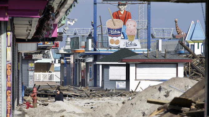 FILE - In this Nov. 22, 2012 file photo, a woman walks past debris from the damaged boardwalk in Seaside Heights, N.J. The iconic boardwalk where generations of families and teens got their first taste of the Jersey Shore and where the reality show of the same name was filmed is being rebuilt following its destruction in Superstorm Sandy. Seaside Heights on Wednesday, Jan. 16, 2013 awarded a $3.6 million contract to have the boardwalk rebuilt in time for Memorial Day weekend.  (AP Photo/Mel Evans, File)