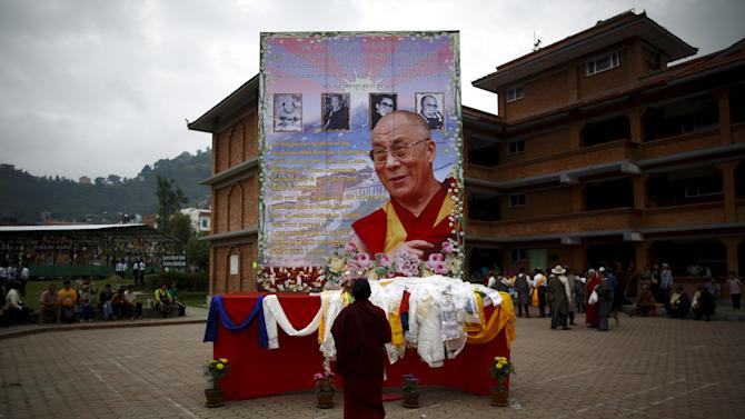 A Tibetan monk offers prayers in front of the portrait of Dalai Lama during his 80th birthday celebration in Kathmandu