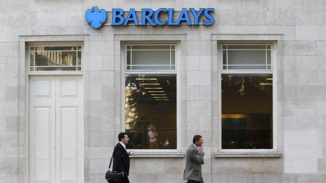 Pedestrians walk past a Barclays bank in London