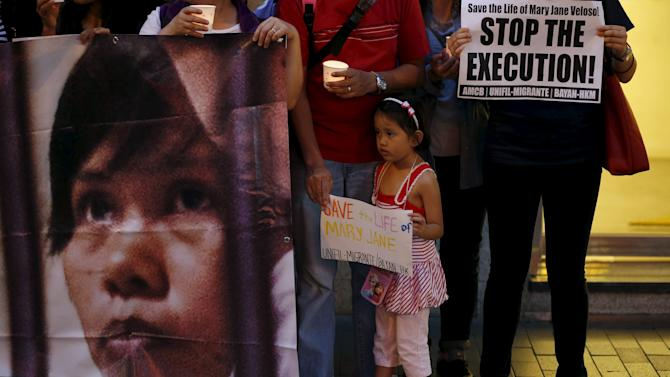 A young Filipina looks on as protesters  carrying a banner appeal for the pardon of Mary Jane Veloso outside the Indonesian consulate in Hong Kong