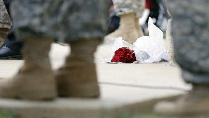 Roses left for shooting victims are seen at the feet of Lt. Gen. Mark Milley, U.S. Sen. John Cornyn, and other military during a news conference near Fort Hood's main gate, Thursday, April 3, 2014, in Fort Hood, Texas. A soldier opened fire Wednesday on fellow service members at the Fort Hood military base, killing three people and wounding 16 before committing suicide. (AP Photo/Eric Gay)