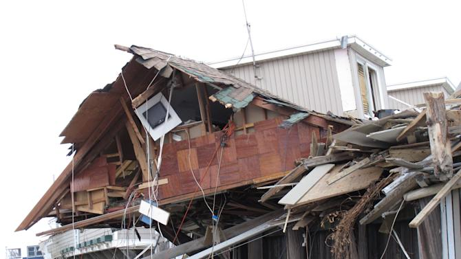 An oceanfront beach club in Sea Bright N.J. lies in ruins on Nov. 15, 2012, two weeks after Superstorm Sandy devastated the town. The entire business district was wiped out (four shops have since re-opened) and 75 percent of residents are still homeless. Yet Sea Bright is determined to rebuild as a debate rages on whether to restore shore communities to their pre-storm condition, or buy out properties in flood-prone areas and depopulate them. (AP Photo/Wayne Parry)