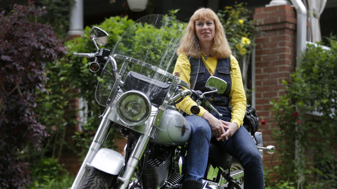 In this Wednesday, May 8, 2013, photo, Crystal Swift poses on her Fat Boy Harley-Davidson at her home in Charlotte, N.C. Harley is the top seller of motorcycles in its class in the U.S. and leads in sales among women, minorities and younger adults as well as the middle-aged men. (AP Photo/Chuck Burton)