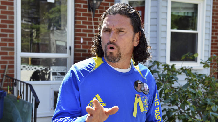 Carlos Arredondo speaks to reporters outside his home while FBI agents waited inside in the Roslindale neighborhood of Boston, Wednesday, April 17, 2013. Arredondo, a peace activist who's son was killed during the Iraq war, was near the explosions and assisted viticims after a  pair of bombs exploded at the finish line of the Boston Marathon Monday. (AP Photo/Josh Reynolds)