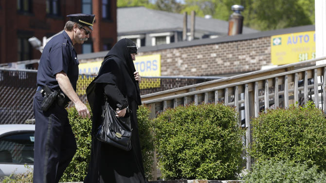 A police officer escorts a woman in Muslim dress into an entrance to the Graham, Putnam, at Mahoney Funeral Parlors in Worcester, Mass., Monday, May 6, 2013 where the body of slain Boston Marathon bombing suspect Tamerlan Tsarnaev is being prepared for burial. Funeral director Peter Stefan has pleaded for government officials to use their influence to convince a cemetery to bury Tsarnaev, but so far no state or federal authorities have stepped forward. (AP Photo/Elise Amendola)