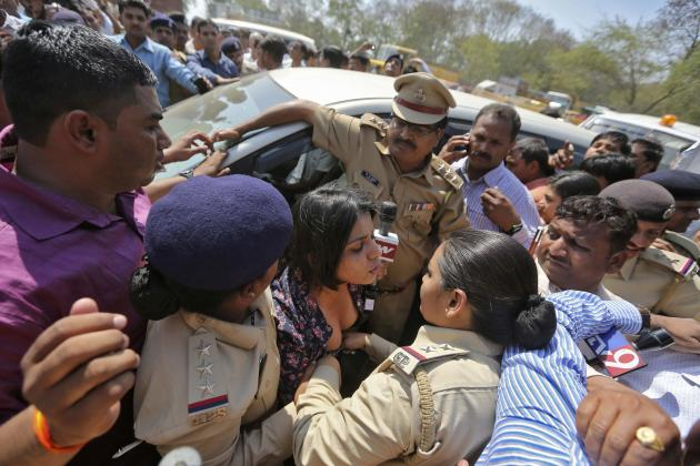 An Indian media personnel argues with police next to a car carrying Delhi's former CM and the chief of the AAP Kejriwal at Sargasan village