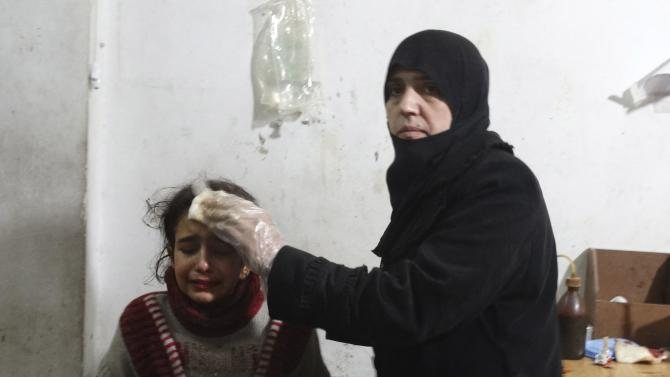 A woman tends to a wounded girl after what activists said was an airstrike by forces loyal to Syria's President Bashar al-Assad, in the Damascus suburb of Saqba