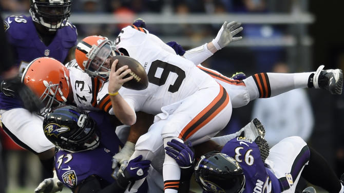 Cleveland Browns quarterback Connor Shaw (9) is taken down by Baltimore Ravens outside linebacker Terrell Suggs, bottom left, and defensive end DeAngelo Tyson in the second half of an NFL football game, Sunday, Dec. 28, 2014, in Baltimore. (AP Photo/Gail Burton)