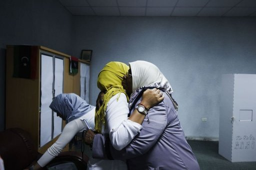 Libyan election workers embrace each other after the ringing of a bell marking the end of voting