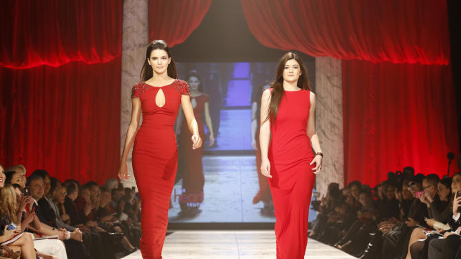 Kendall Jenner, left, and Kylie Jenner walk the runway at the Red Dress Collection 2013 Fashion Show, on Wednesday, Feb. 6, 2013 in New York. (Photo by John Minchillo/Invision/AP)