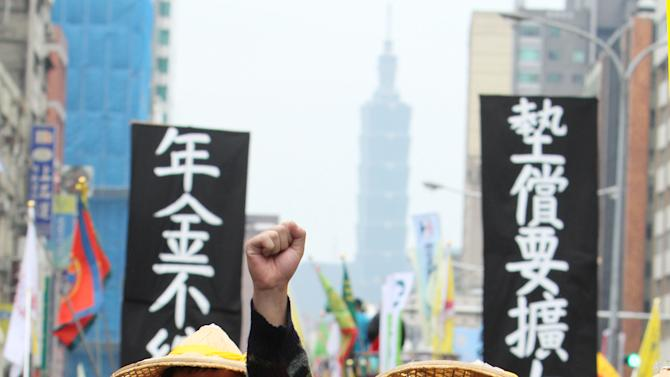 Taiwanese workers shout slogans during a protest on May Day in Taipei, Taiwan, Wednesday, May 1, 2013.  More than 10,000 Taiwanese workers took to the streets in Taipei Wednesday to protest a government reform plan that will cut pension payouts to ease Taiwan's worsening fiscal problems. The protesters said the payout cuts reflect a longstanding government policy to bolster economic growth at the expense of workers' benefits  and compromised workplace safety. (AP Photo/Chiang Ying-ying)