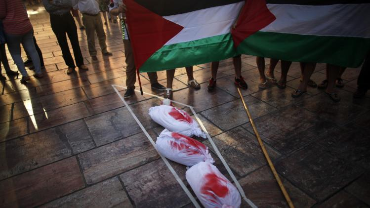 People hold Palestinian flags next to sheets stained in red paint on July 16, during a protest against Israel's military action in Gaza