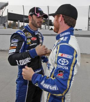 Jimmie Johnson, left, gets a handshake and hug from Brian Vickers, right, after qualifying for Sunday's Sprint Cup race at Martinsville Speedway  in Martinsville, VA., Friday, Oct. 26, 2012.  Johnson won the pole and Vickers was second.  (AP Photo/Steve Helber)